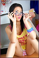 Kieko Kyo Sitting On Wooden Floor Playing With Spectacles Flash Of Panties