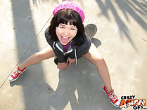 Xhivi Kim sitting on pavement wearing pink hat in red sneakers