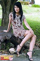 Sitting On Tree Stump Wearing Dress In High Heels