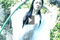 Ivy stripping raincoat outdoors playing with garden hose